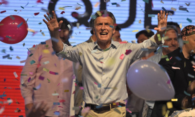 Argentine presidential candidate Mauricio Macri gestures at supporters at the party's headquarters in Buenos Aires on October 25, 2015. Buenos Aires Governor Daniel Scioli led Argentina's presidential election race as counting got under way Sunday, but it was unclear whether he would avoid a runoff against his conservative rival Mauricio Macri.  AFP PHOTO / EITAN ABRAMOVICH        (Photo credit should read EITAN ABRAMOVICH/AFP/Getty Images)